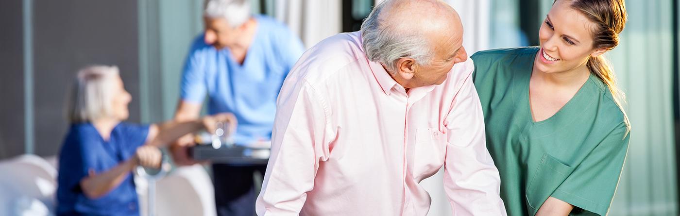 Liebevolle Pflegerin führt Patienten bei Zeitarbeit in Essen